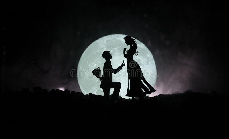 Amazing love scene. Silhouettes of man making proposal to woman or Silhouettes of couple against big moon at background. Selective focus stock illustration