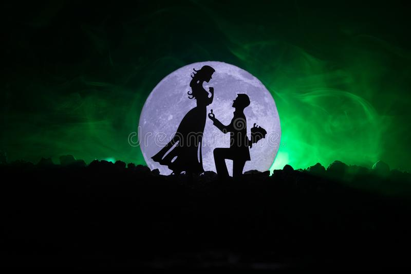 Amazing love scene. Silhouettes of man making proposal to woman or Silhouettes of couple against big moon at background. Selective focus royalty free illustration