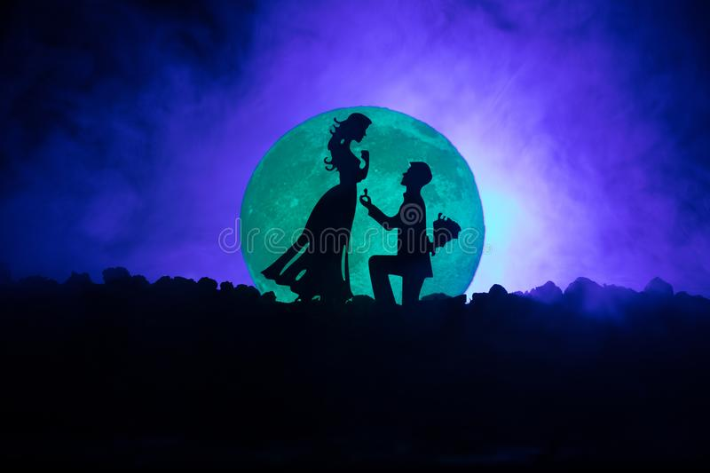 Amazing love scene. Silhouettes of man making proposal to woman or Silhouettes of couple against big moon at background. Selective focus vector illustration