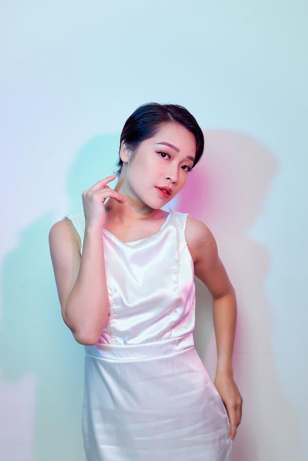 Amazing luxury seductive woman in stylish white party dress posing on white wall.  Fashion portrait. Celebrating birthday party. Amazing luxury seductive woman stock image