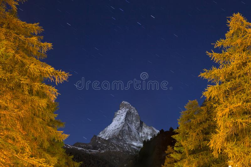 Amazing Matterhorn mountain at twilight, blue skies with Star Trail. And with orange pines stock photography