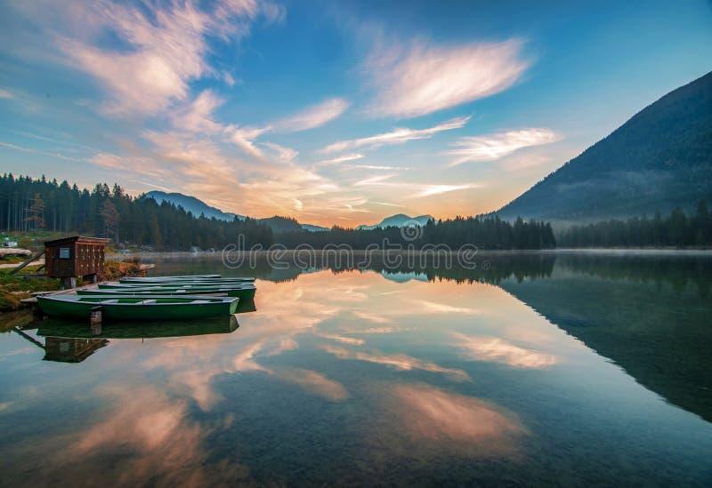 Amazing morning scenery with boats moored on Hintersee lake at sunrise. Amazing morning scenery with boats moored on Hintersee lake. Picturesque clouds coloured stock photo