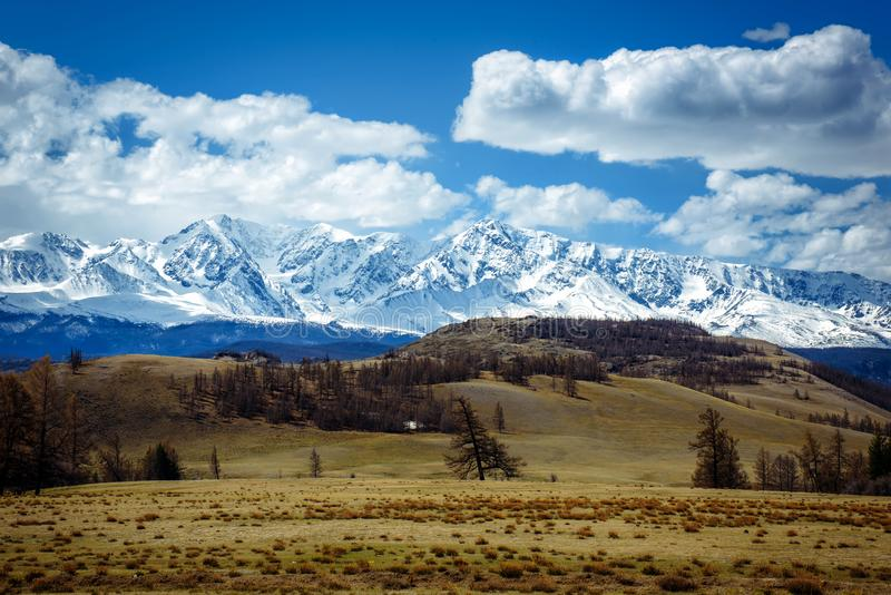 Amazing mountain landscape. Rocky mountains with snowy peaks, hills covered with grass in the Alpine scene on a bright sunny day. With blue sky and clouds. View stock image