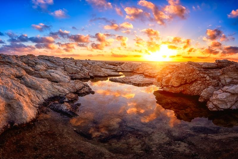 Amazing nature landscape, colorful sunset on the white rocks. With sun, blue sky, clouds and reflection in the water, Cyprus. Outdoor travel background royalty free stock images