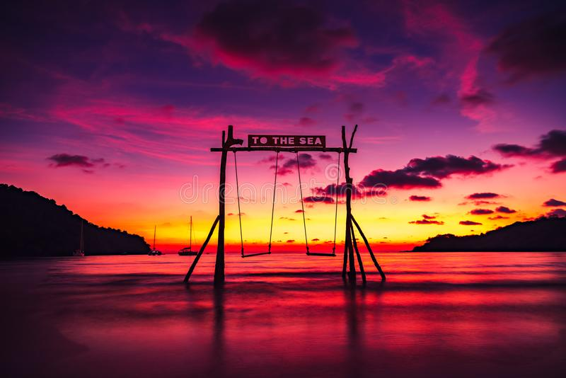 Scenic swings in the sea for a couple of lovers in love with a beautiful sunset. Amazing nature landscape tropical beach with scenic swing in sea on background stock photography