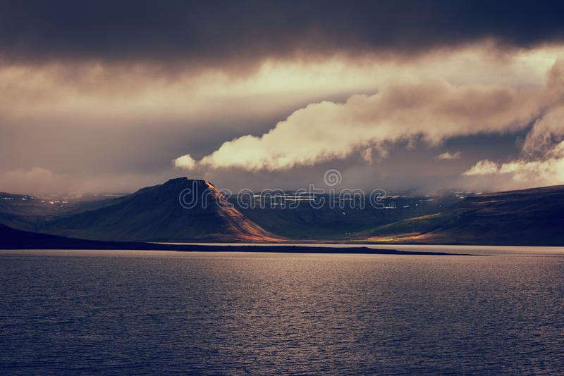 Amazing nature, night scenic landscape in moonlight with water, volcanic mountains and cloudy sky, Iceland. Travel outdoor stock images