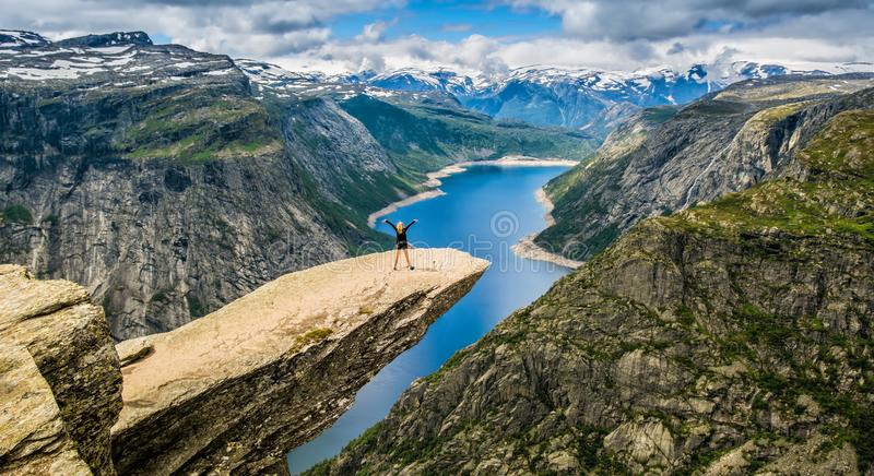 Amazing nature view with Trolltunga and a girl standing on it royalty free stock photos