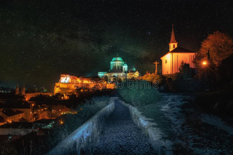 Amazing night scenery of Esztergom, Hungary under starry sky. Calvary and Sorrowful Virgin Chapel on foreground and royal castle and famous Basilica of royalty free stock photos