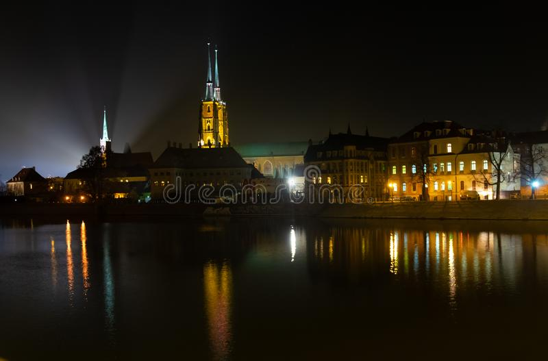 Amazing night view on beautiful illuminated Cathedral of St. John the Baptist reflected in Oder river. Ostrow Tumski district. Wroclaw. Poland stock images