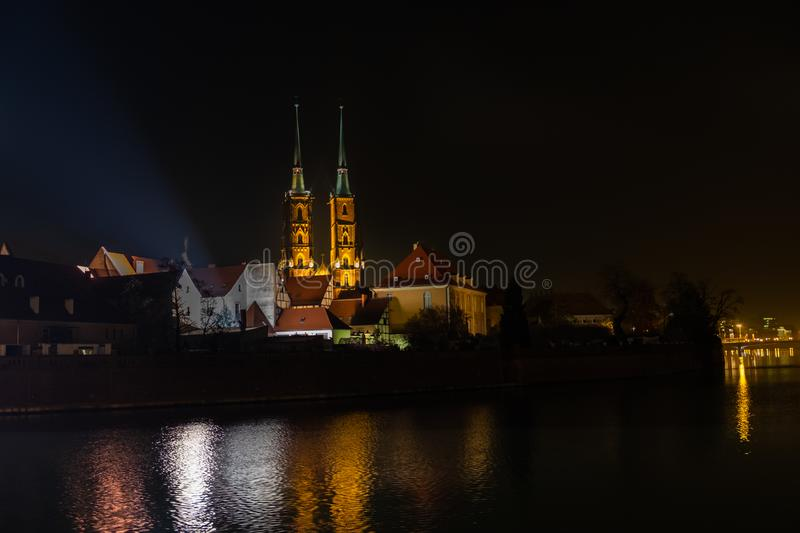 Amazing night view on beautiful illuminated Cathedral of St. John the Baptist reflected in Oder river. Ostrow Tumski district. Amazing night view of the stock images