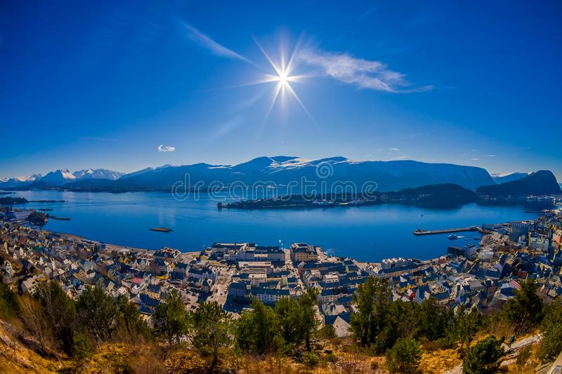 Amazing outdoor view of colorful buildings from the mountain Aksla at the city of Alesund with a huge mountain behind. With sun shine at the blue sky in Norway stock photos