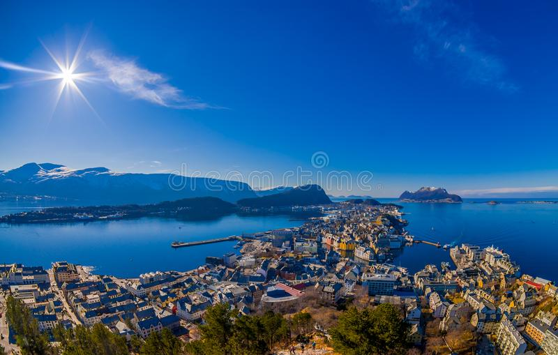 Amazing outdoor view of colorful buildings from the mountain Aksla at the city of Alesund with a huge mountain behind. With sun shine at the blue sky in Norway stock images