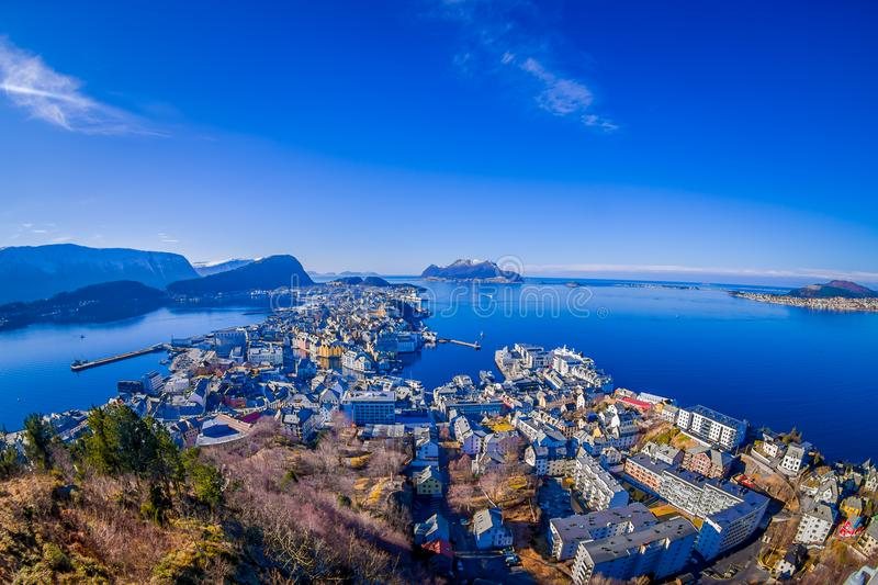 Amazing outdoor view of colorful buildings from the mountain Aksla at the city of Alesund with a huge mountain behind. In Norway, fish eye effect royalty free stock photography