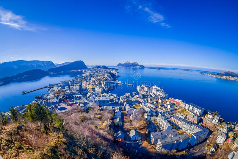 Amazing outdoor view of colorful buildings from the mountain Aksla at the city of Alesund with a huge mountain behind. In Norway, fish eye effect royalty free stock photos