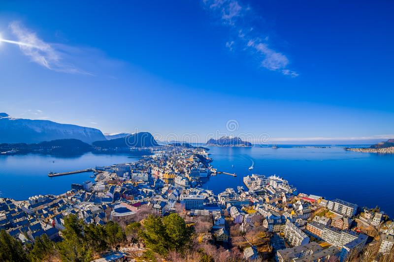 Amazing outdoor view of colorful buildings from the mountain Aksla at the city of Alesund with a huge mountain behind. In Norway, fish eye effect stock image