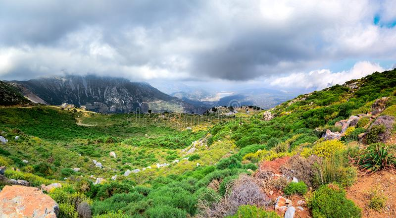 Amazing panorama of rough wild mountains, grass, cloudy blue sky, Lasithi, Crete. Greece royalty free stock photo