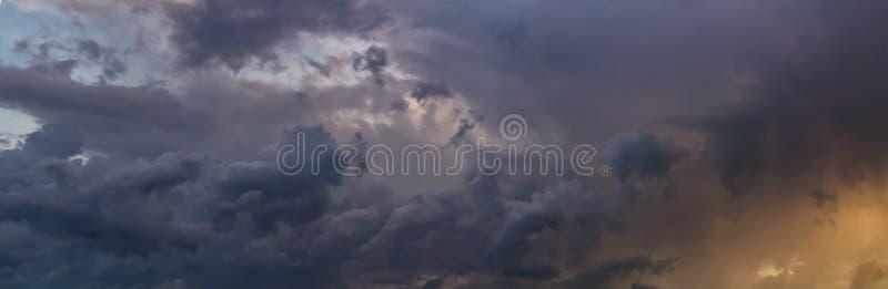 Amazing panoramic storm rainy cloud with blue sky and orange sun.  royalty free stock photo