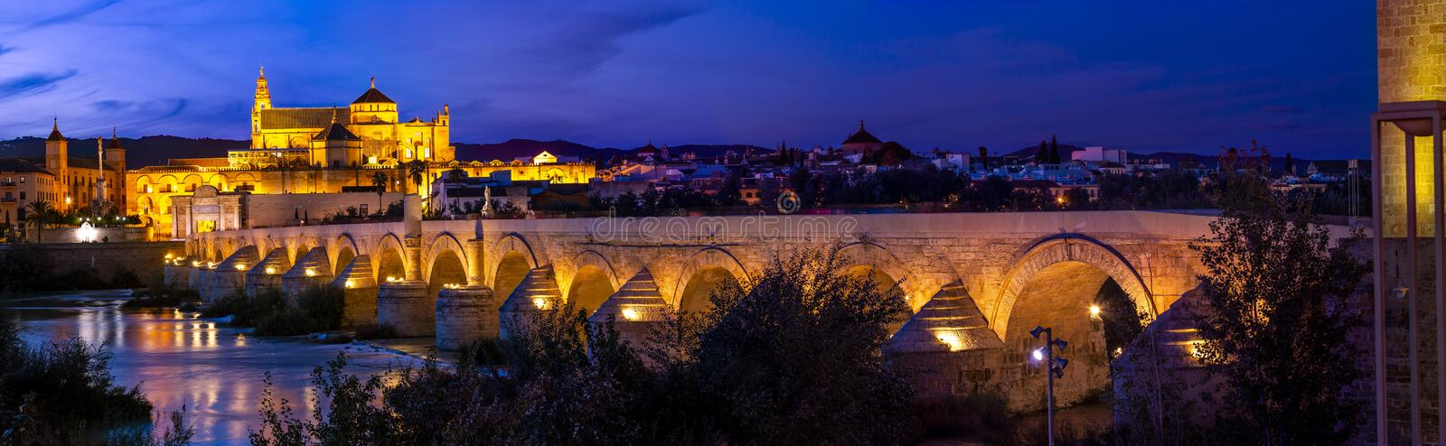 Amazing panoramic view of Roman bridge and Mezquita of Cordoba glowing in night royalty free stock images