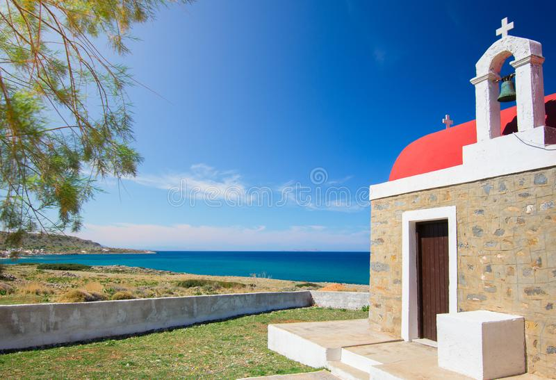 Amazing pictorial view of an old stone church beside blue sea, Milatos, Crete. royalty free stock photos
