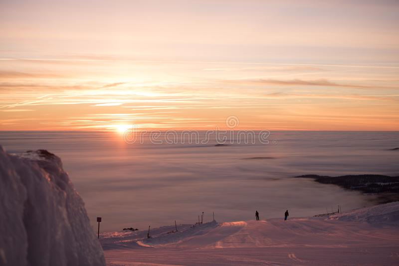 Amazing pink sky and mountain all around. Friends having fun on top of the mountain while skiing/snowboarding. Breathtaking sunset royalty free stock image