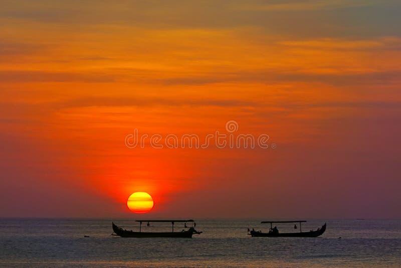 Amazing red sun sunset with fisherman`s boats silhouettes, Kuta beach, Bali. Amazing color red sun sunset with fisherman`s boats silhouettes, Kuta beach, Bali stock photography