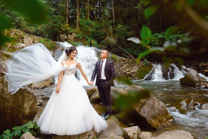 Amazing romantic view of happy bride with groom near beautiful grand waterfall in mountain. luxurious wedding dress. Marriage coup royalty free stock image
