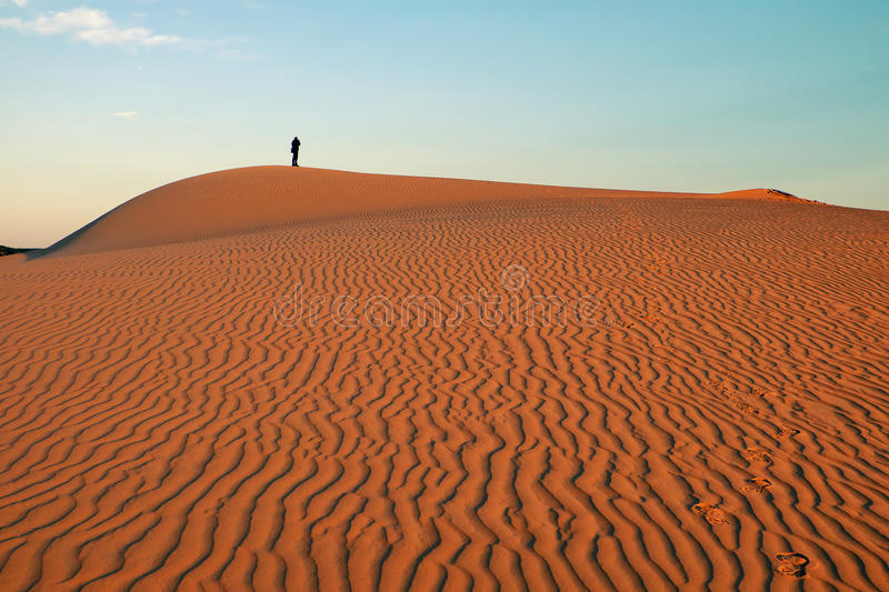Amazing sand hill to adventure travel for summer trip. Amazing shape on Vietnamese sand hill at Bau Trang, Mui Ne, Vietnam. Lonely man walking on sandy to take royalty free stock images