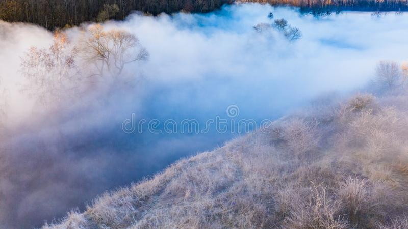 Amazing scenery. Dense fog covering small river aerial landscape. Nature concept royalty free stock images
