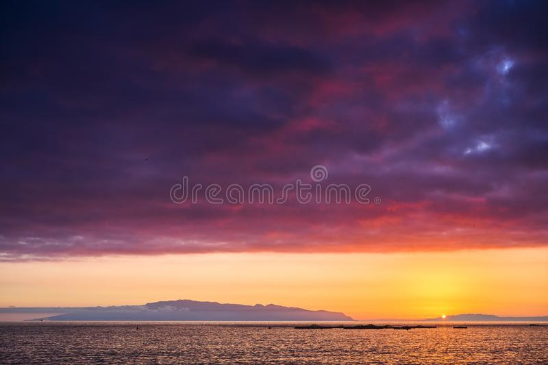 Amazing scenic landscape taken during a wonerful sunset on the ocean. La Gomera oceanic island in background with clouds and water royalty free stock image