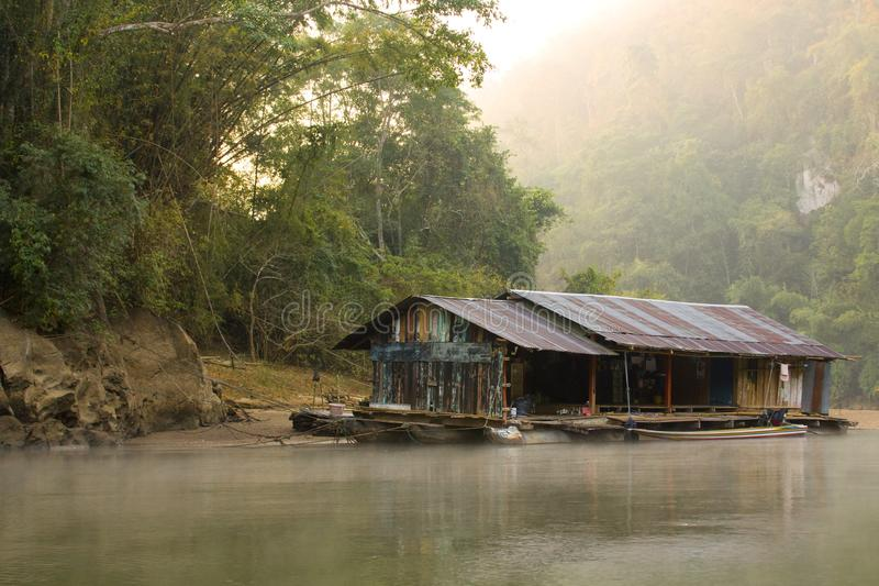 Amazing scenic view tropical forest with jungle river on background green trees in the morning rays of the sun. Amazing scenic view of the old house on the river royalty free stock photography