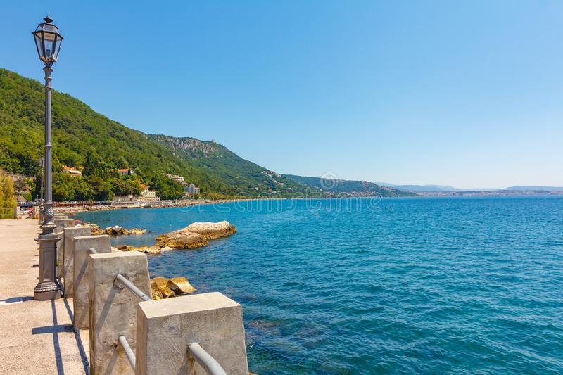 Amazing seaside view of blue Adriatic sea with azure water and blue sky. There is a lamp on the sea coast in front of green royalty free stock photos