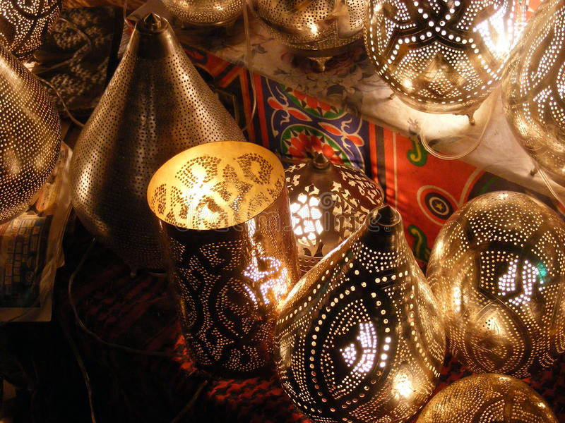 Amazing Shining lanterns in khan el khalili souq market with Arabic handwriting on it in egypt cairo. Vendor selling handmade copper oriental lamps ornaments in royalty free stock image