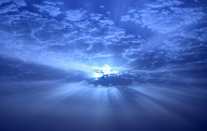 Amazing sky at sunrise with rays through the clouds. Amazing sky with sunbeams through the clouds at dawn, photographic image with color digital effects stock images