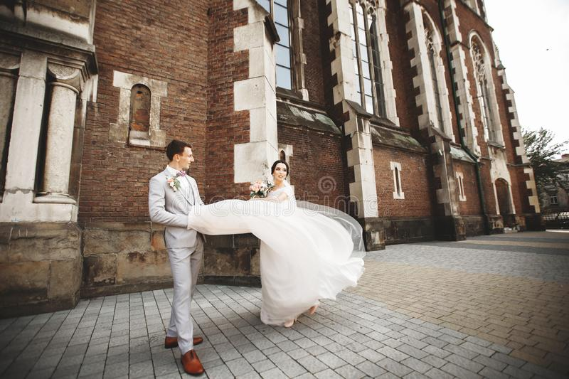 Amazing smiling wedding couple. Pretty bride and stylish groom near the church royalty free stock images