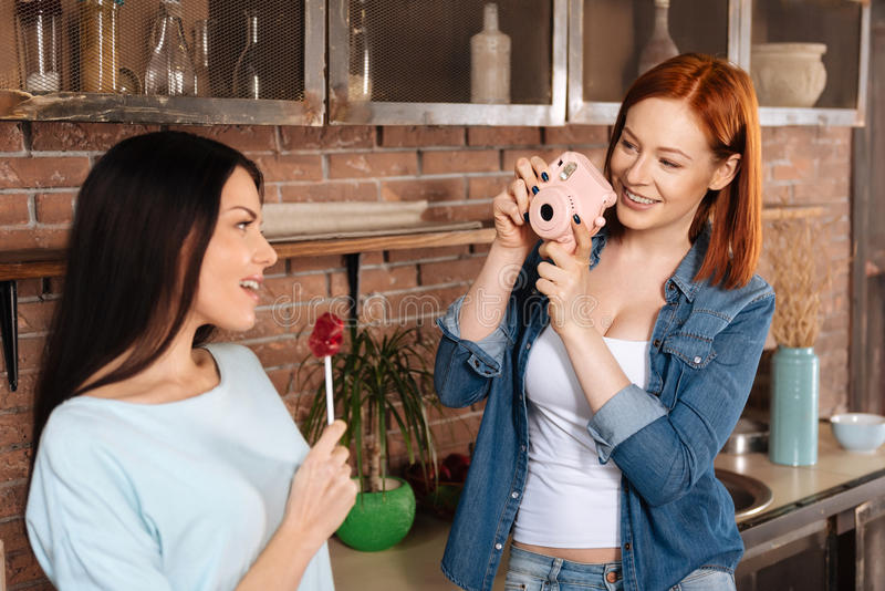 Amazing smiling woman holding camera. Look at me. Positive delighted women wearing casual clothes holding photo camera in front of face while shooting her friend royalty free stock image