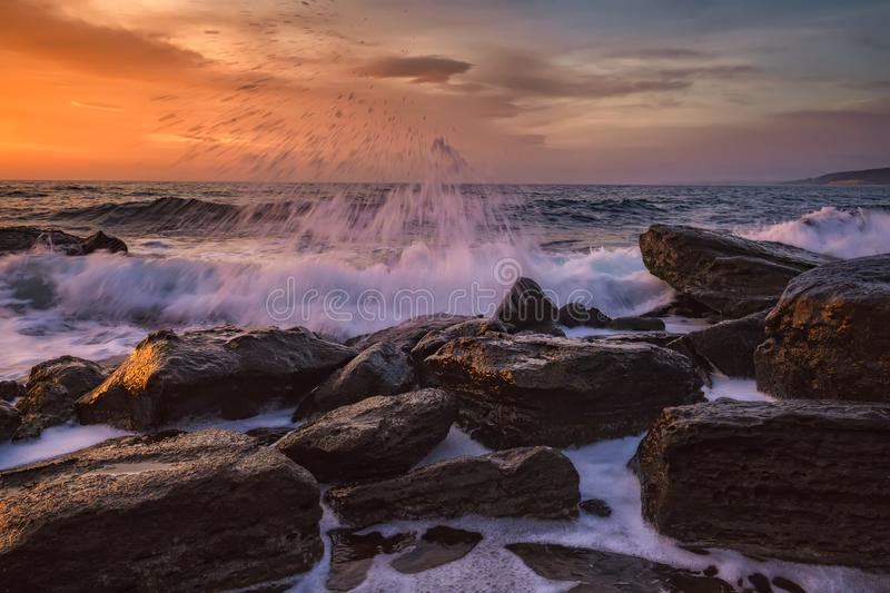 Beautiful motion blur sea waves over the rocks royalty free stock images