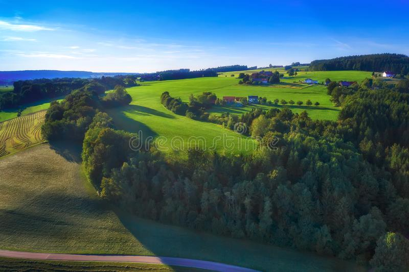 Amazing spring landscape with green rolling hills and farmhouses royalty free stock photo
