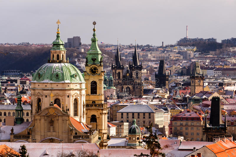 Amazing St. Nicolas church during winter day after heavy snow storm with snow cover at roofs. Prague, Czech republic. stock image