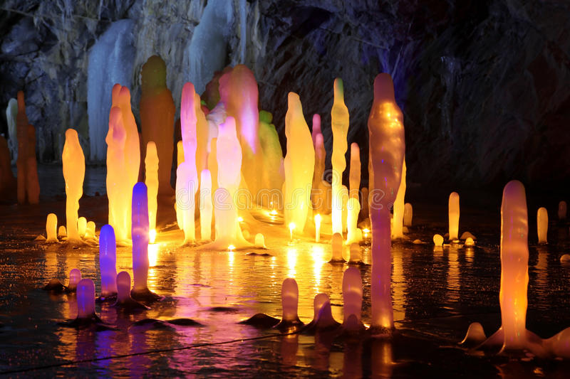 Amazing stalagmite illuminations in cave. Amazing stalagmite illuminations with help candels and light in deep cave, North Europe royalty free stock photos