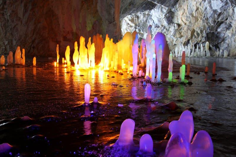 Amazing stalagmite illuminations in cave. Amazing stalagmite illuminations with help candels in deep cave, North Europe royalty free stock photos