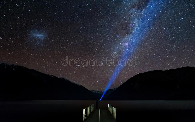 Amazing Starry night at Lake Rotoiti. Milky way and the galaxy. A man lighting the headlamp in the sky. Nelson Lake National Par royalty free stock image
