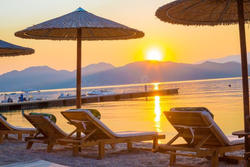 Amazing sunrise in Corfu island in summer holiday, Greece. Beautiful vibrant sunrise on the beach among chair and umbrellas in Corfu island, summer holiday stock photo
