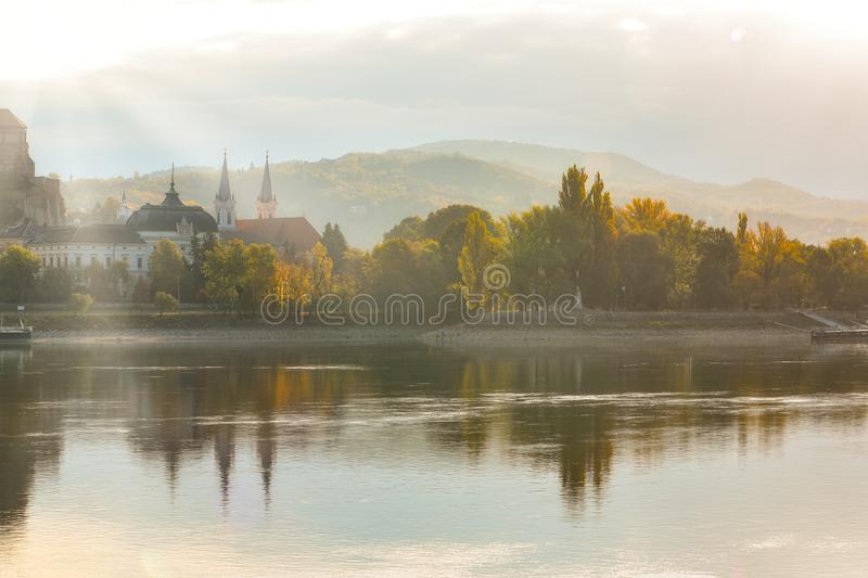 Amazing sunrise view over Danube river, Esztergom, Hungary. Amazing sunrise view over Danube river. Autumn yellow trees illuminated by rising sun and mirrored in royalty free stock image