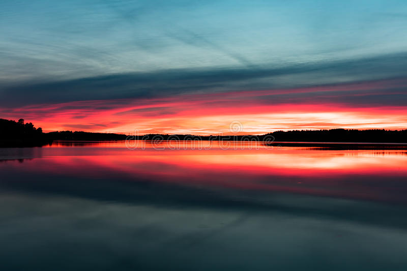 Amazing sunset colors. Amazing sunset above sea and forest with vivid colors and reflection on the calm water surface