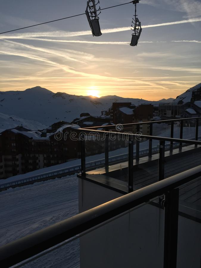 High chair lift in th sky in fornt of the sunset in french alps. Amazing sunset fith chair lift in high slops, from the french alps royalty free stock image