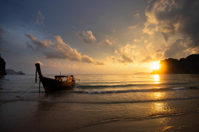 Amazing sunset with longtail boats silhouette at Railay beach, Thailand royalty free stock image