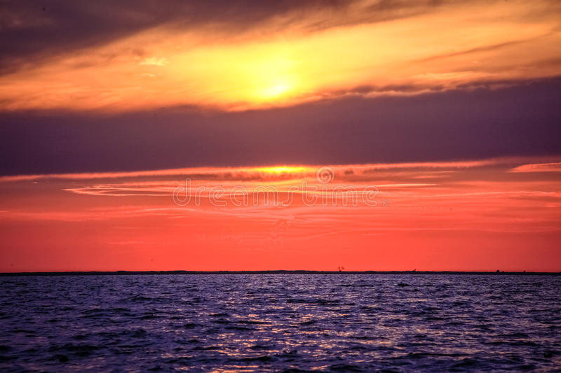 Amazing Sunset over an ocean with clouds stock image