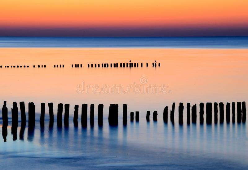 Amazing sunset over the sea. Baltic. Red, pink, violet, orange and dark blue light. The sky is reflected in the calm sea. Old wooden breakwaters are royalty free stock images
