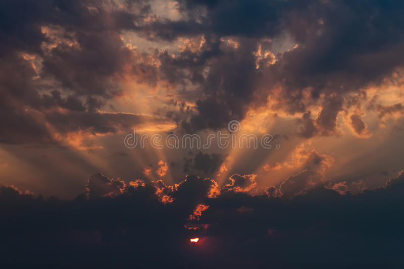 Amazing sunset with powerful sunbeams. Inspiring sunset over cultivated land with dramatic sky, clouds and sunbeams stock image
