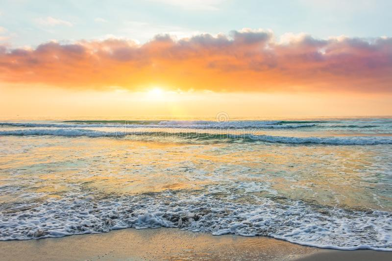 Amazing sunset on a sandy beach of an island in the ocean stock photo
